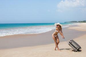 Frau mit Koffer am Strand